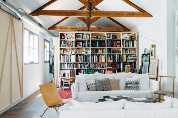 La casa del designer Alvaro Catalán de Ocón - living con divano Ghost in lino bianco, poltroncina PK22 di Poul Kjaerholm, libreria