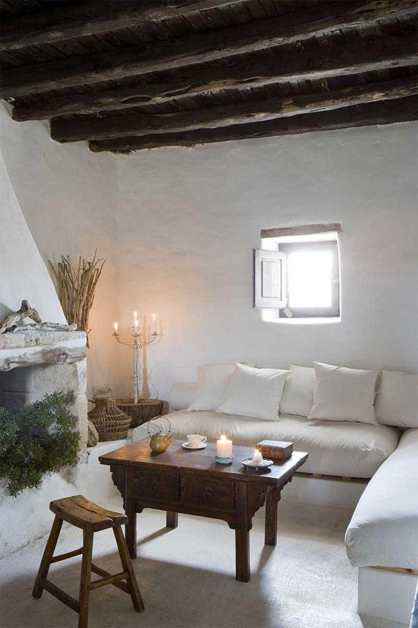 rifugio a Formentera - living con travi a vista, divano bianco, tavolino in legno, candele